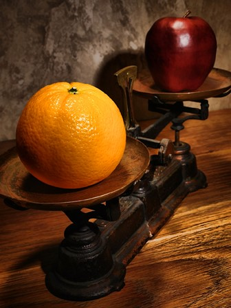 comparing an apple and an orange on an antique scale