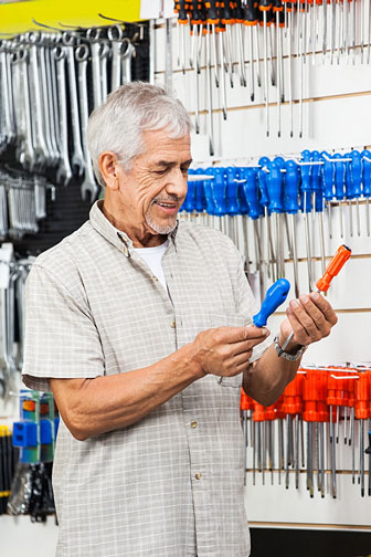 customer comparing screwdrivers in a hardware store
